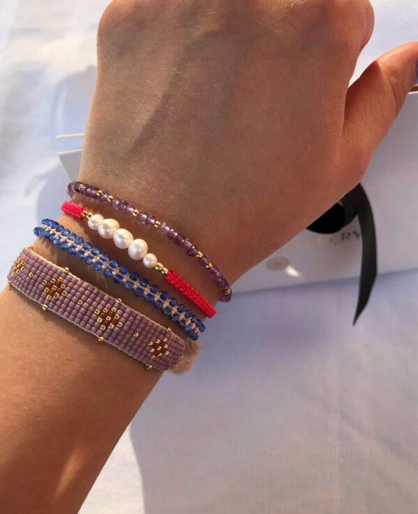 Bransoletka pleciona na cienkim, koralowym sznurku z perełkami i srebrem