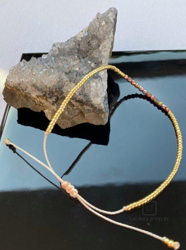 Bransoletka na cienkim beżowym sznureczku ze złotymi koralikami i hematytami