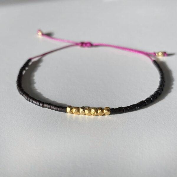 Bransoletka na cienkim bordowym sznurku z czarnymi koralikami i srebrem