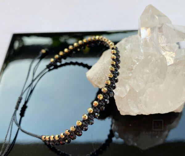 Bransoletka na czarnym sznurku, przeplatana naturalnymi spinelami i hematytami